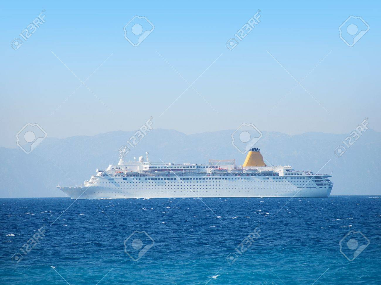 Big Cruise Vessel Side View With Water Surface In Front And Mainland Back Stock