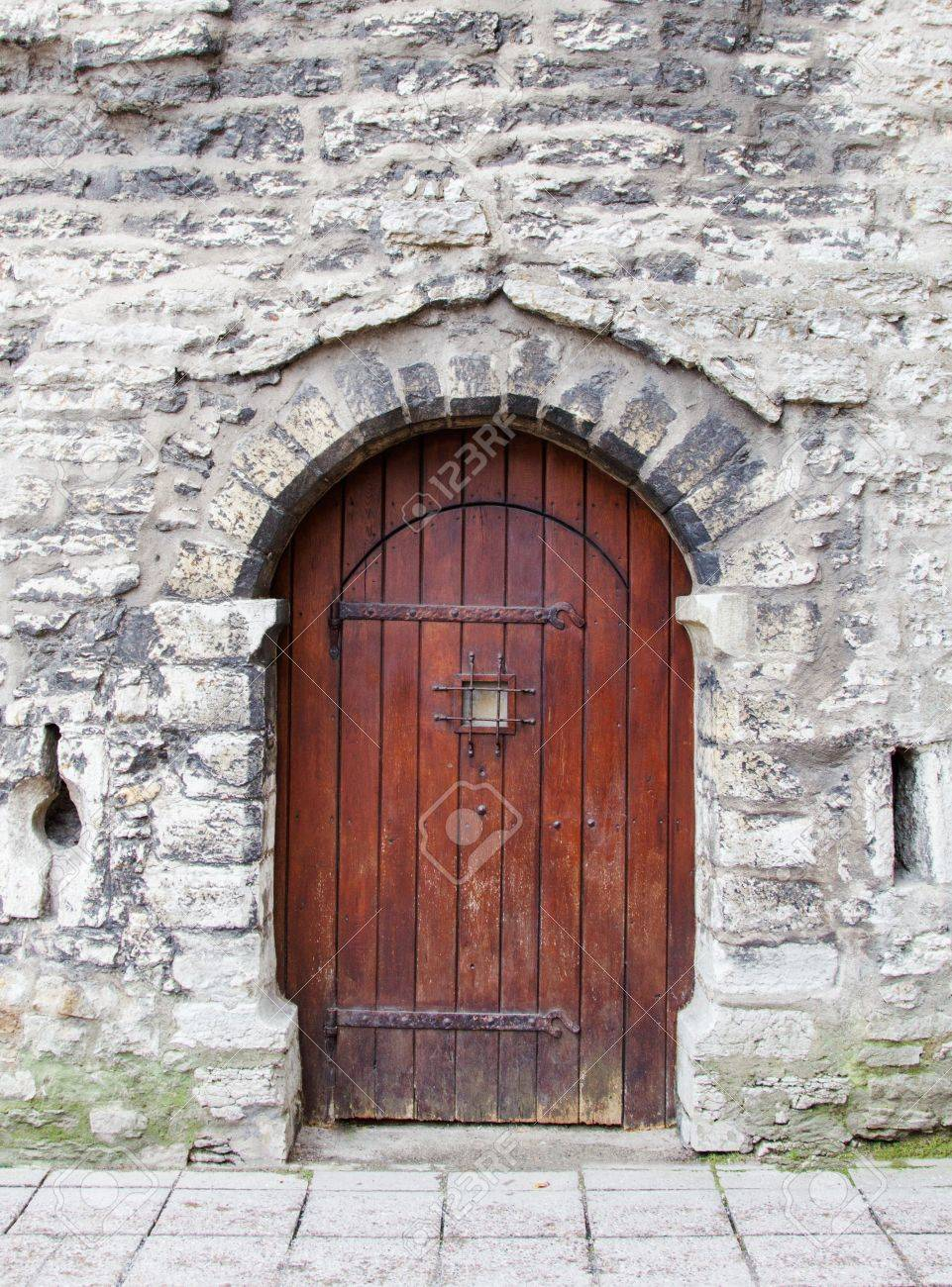 Old wooden arched door in stone wall. Stock Photo - 16556037