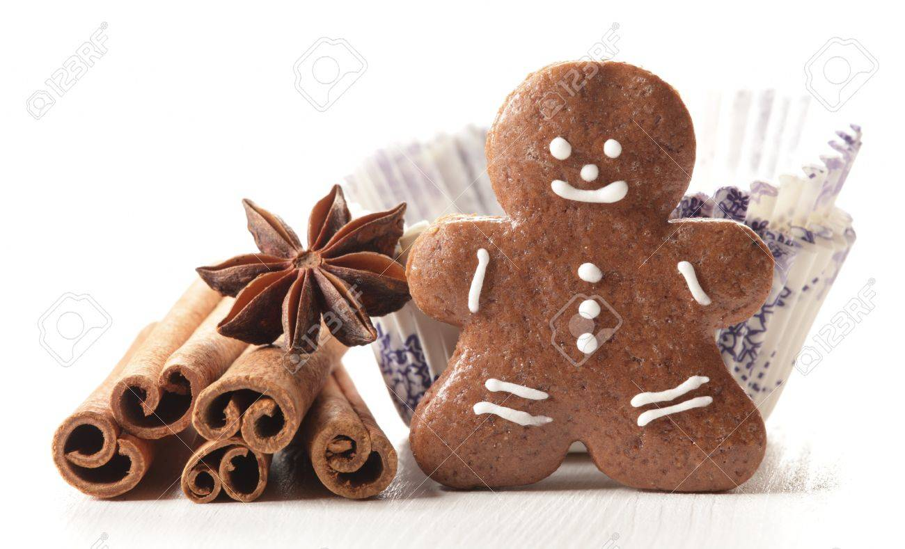 Close-up of gingerbread man, vanilla beans, anise stars, cinnamon sticks in paper cupcakes on white background Stock Photo - 20860408