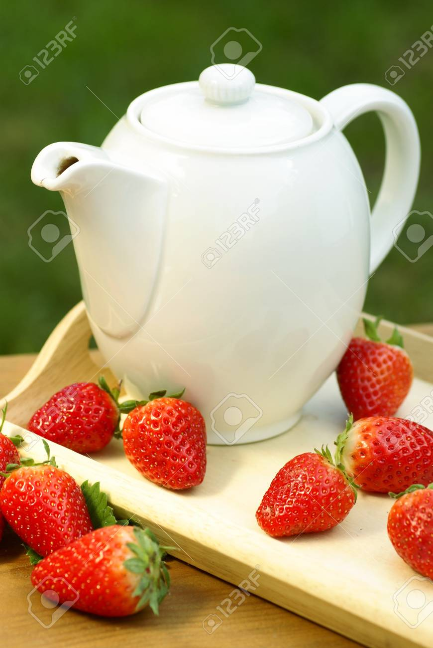 Jug with tea or coffee and strawberries. Stock Photo - 21994971