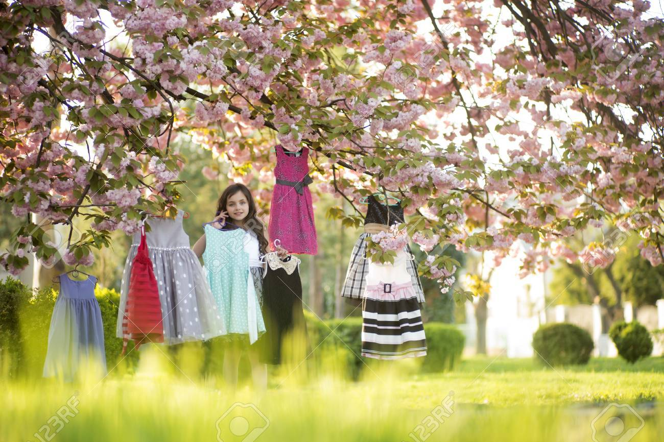 Small Cute Girl Looking Forward Choosing Colorful Baby Clothes