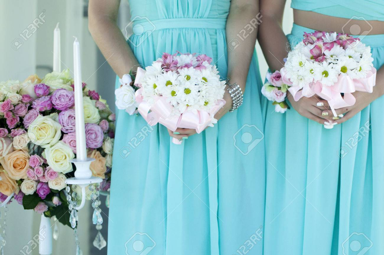 Two Bridesmaids In Light Sky Blue Dressed Holding Soft White