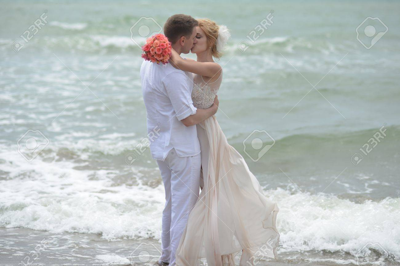 Beautiful Young Wedding Couple Of Kissing Man And Woman In Beige ...