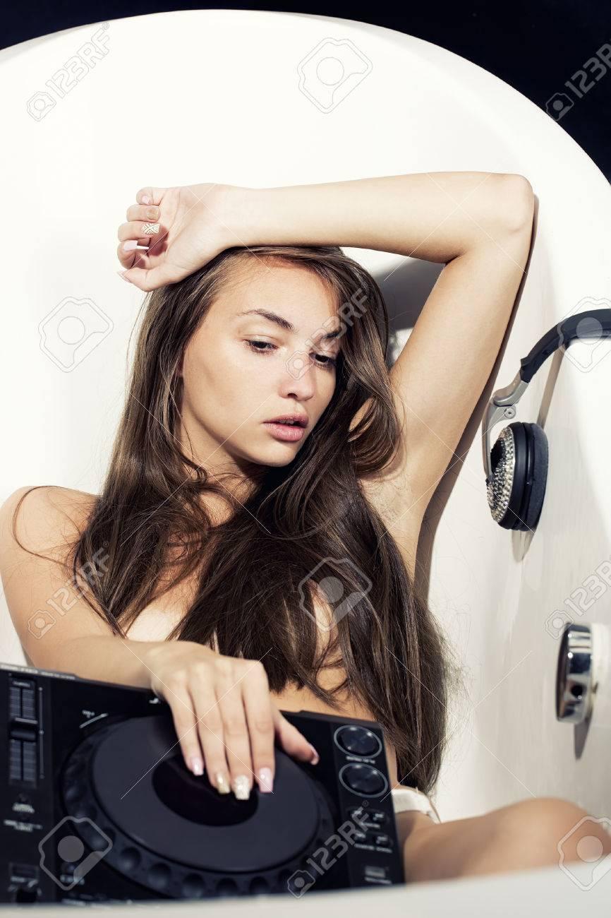 Hermosa Sensual Sexy Dj Chica Joven Desnuda Con El Pelo Largo Acostado En La Bañera Blanca Jugando En La Consola Del Mezclador Musical Con Glamour