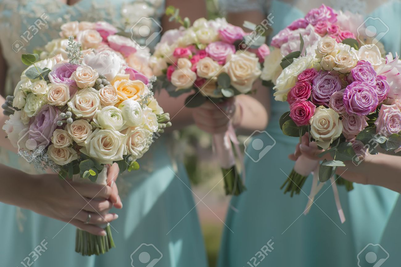 Three beautiful fresh wedding bouquets of colorful rose flowers stock photo three beautiful fresh wedding bouquets of colorful rose flowers pink violet lilac purple white orange and yellow in hands of bride and mightylinksfo