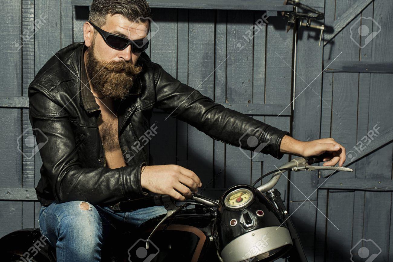chaussures élégantes inégale en performance fournisseur officiel Beau brutale motard mâle rasé avec une longue barbe brune jeans veste en  cuir et lunettes de soleil assis dans le garage sur la moto hâte sur fond  de ...