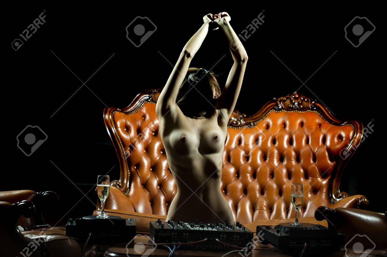 Dj De La Mujer Desnuda Atractiva Erótica En Auriculares Con El Pecho Desnudo Y Pezones De Pie Cerca De La Mesa Con La Consola Mezcladora Y Copa De