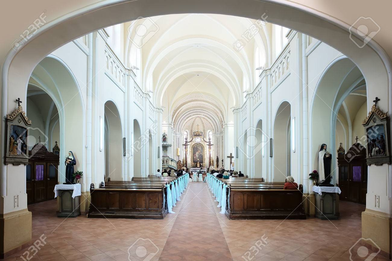 Wedding ceremony in spacious bright columned hall of catholic stock photo wedding ceremony in spacious bright columned hall of catholic church with wooden pews decorated elegant white bows horizontal photo junglespirit Images