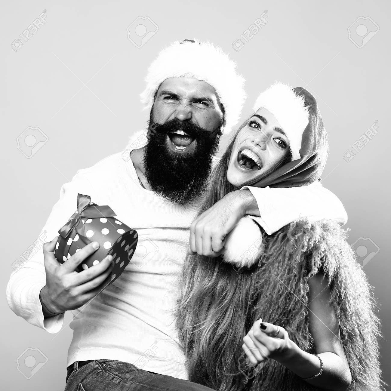 stock photo young beautiful happy new year couple of man with long beard with present box and woman in red santa christmas hat with fur in studio black