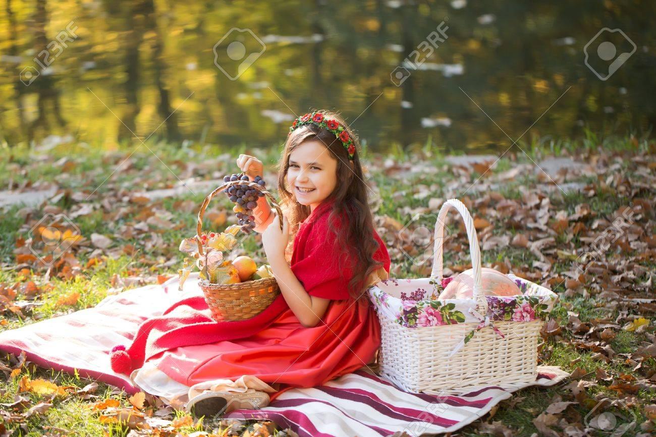 Sourire Petite Fille Dans Des Vêtements Rouges Et Couronne De Fleurs Sur  Les Cheveux Noirs Crépus Tenant Bouquet Bleu De Raisin Sur Plaid Avec Des  Paniers
