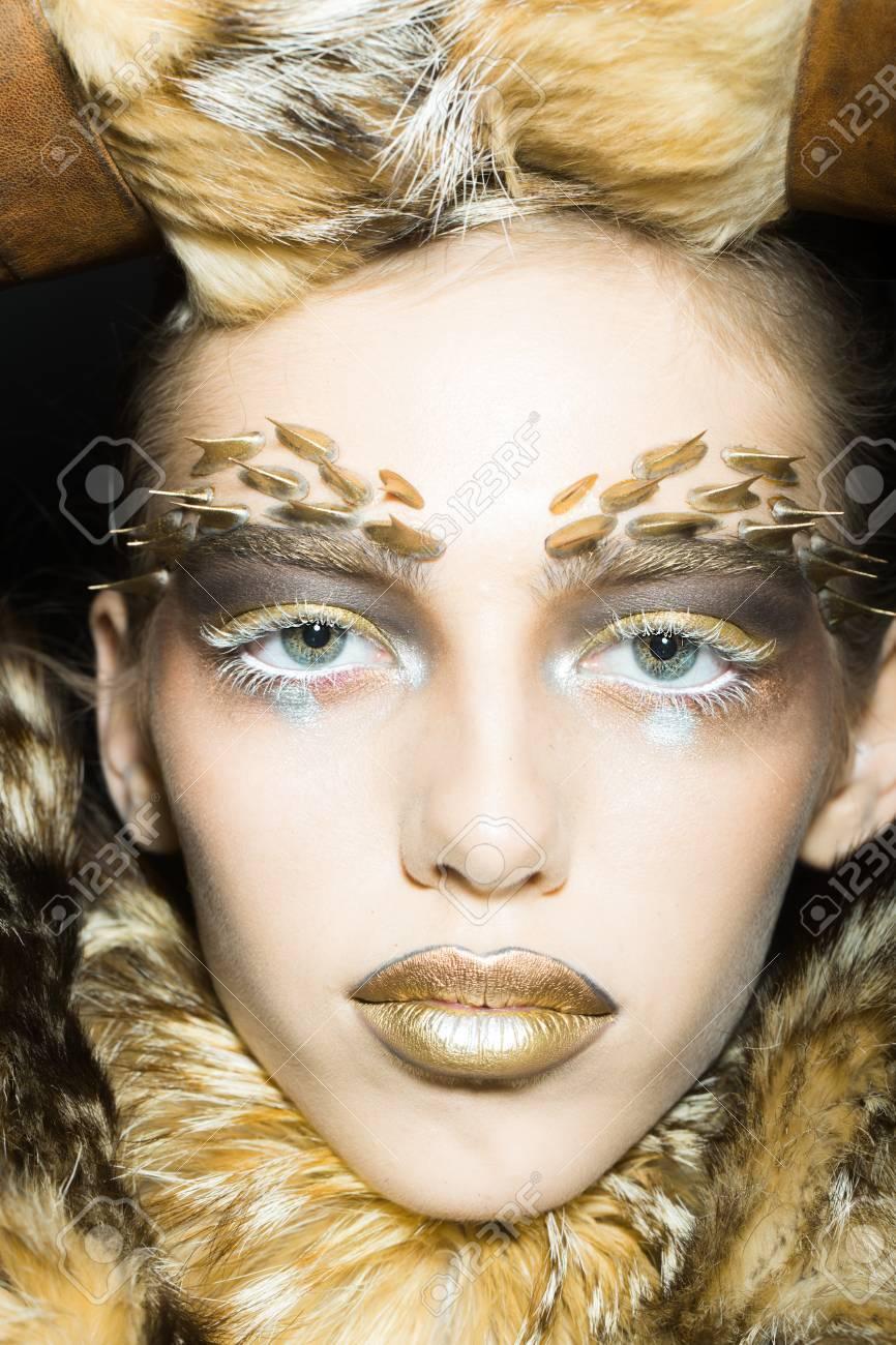 Banque d\u0027images , Portrait Gros plan d\u0027une belle jeune femme sauvage avec  lumineux animaux singe doré maquillage avec des épines sur le visage en  manteau de