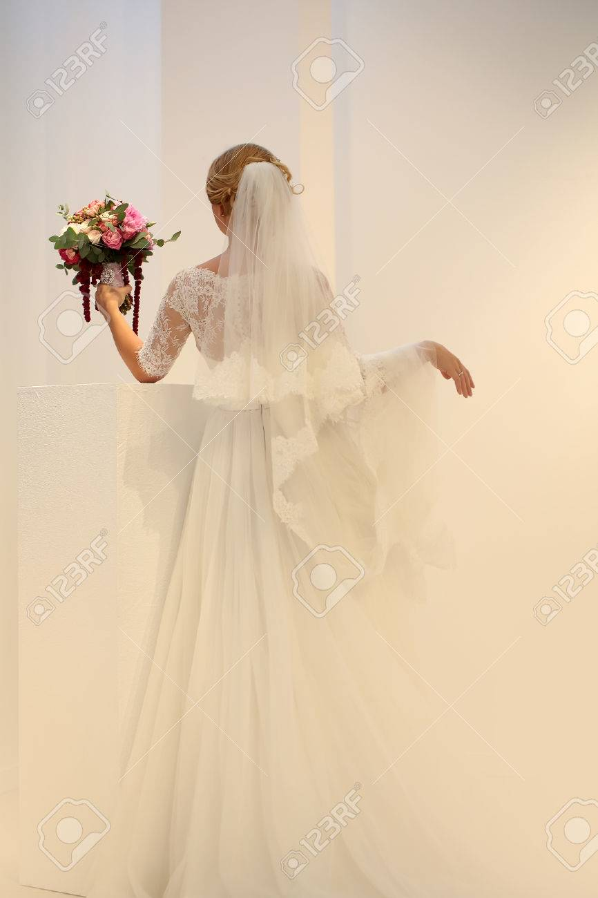 Photo of young bride full length back view wearing long lace..