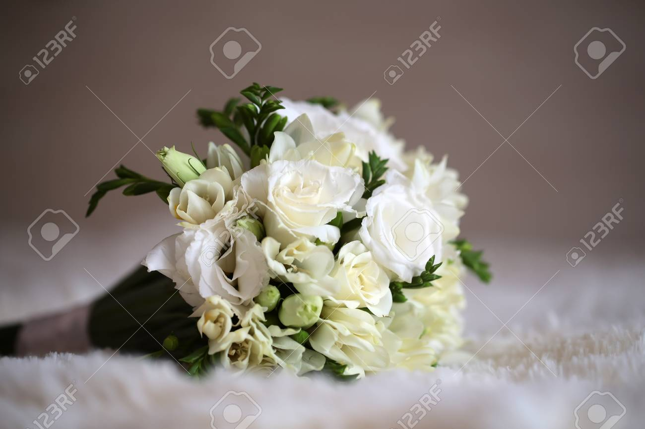 Beautiful tender fresh bridal wedding bouquet of white roses stock beautiful tender fresh bridal wedding bouquet of white roses and creamy tulips with green leaves laying mightylinksfo
