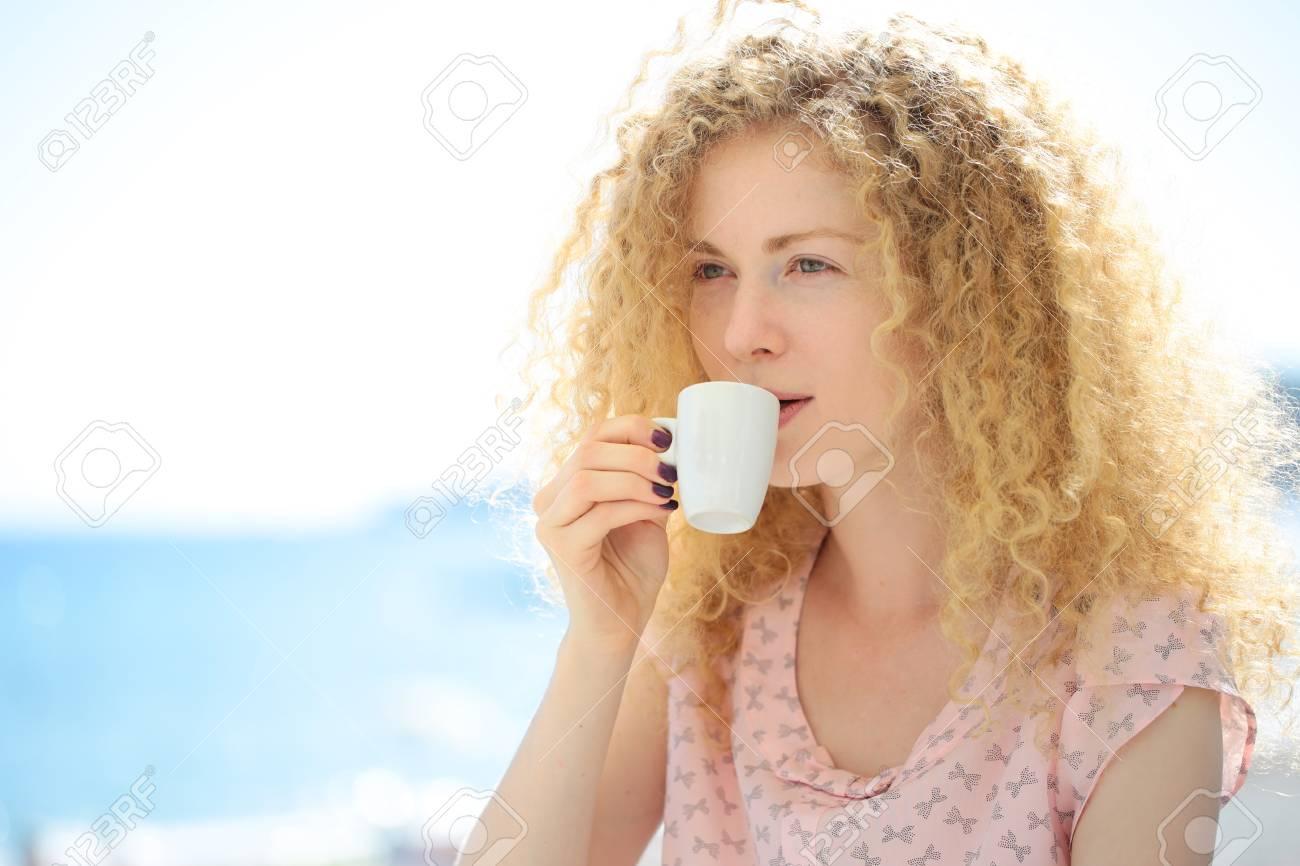 Archivio Fotografico - Donna giovane bella femmina con biondo capelli  biondi lunghi ricci bere caffè all aperto ritratto su sfondo blu offuscata 52fae77de64
