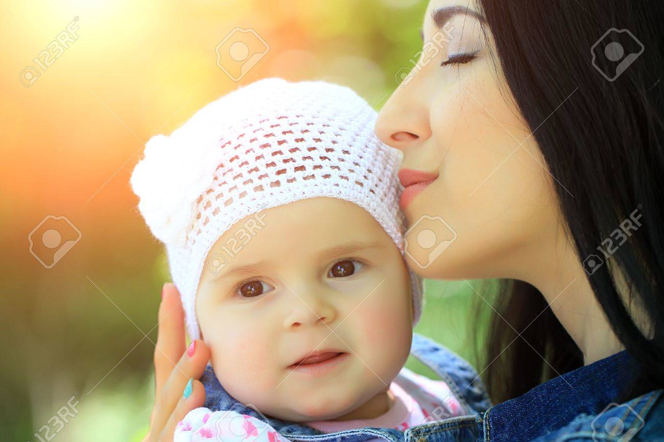 e449b6cf1d2 Mother Kissing And Holding Small Daughter Baby Girl Cute Hazel-eyed ...