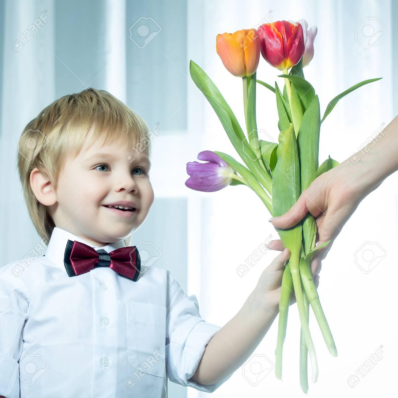 b16ffe4a3 Sonriente Feliz Pequeño Caballero Lindo Chico Con El Pelo Rubio En La Camisa  Blanca Y Pajarita Que Da Hermoso Ramo Fresca Primavera De Tulipanes De  Colores ...