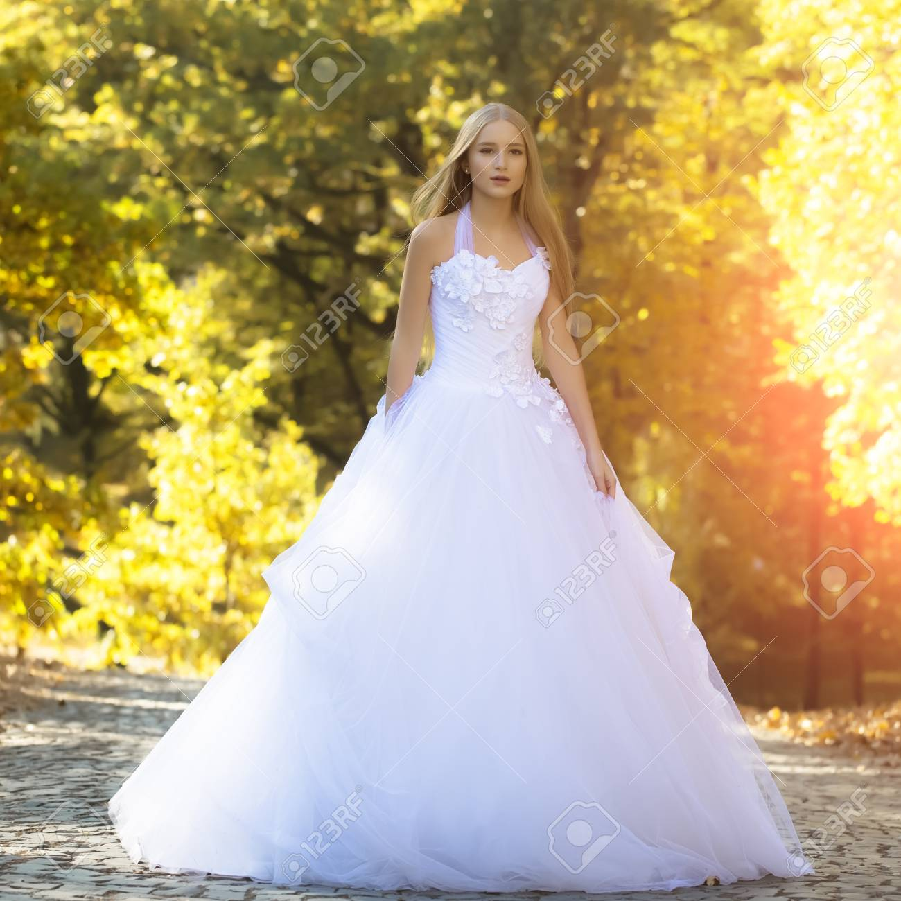a9d6fad2 Pretty sensual thoughtful young bride girl with long blonde hair in beautiful  white wedding dress standing