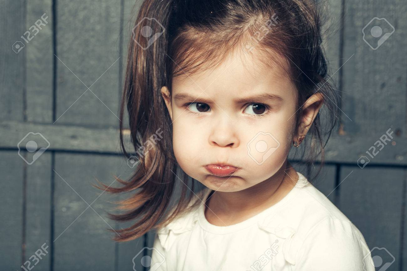 Little girl with cute face and funny hairstyle making faces