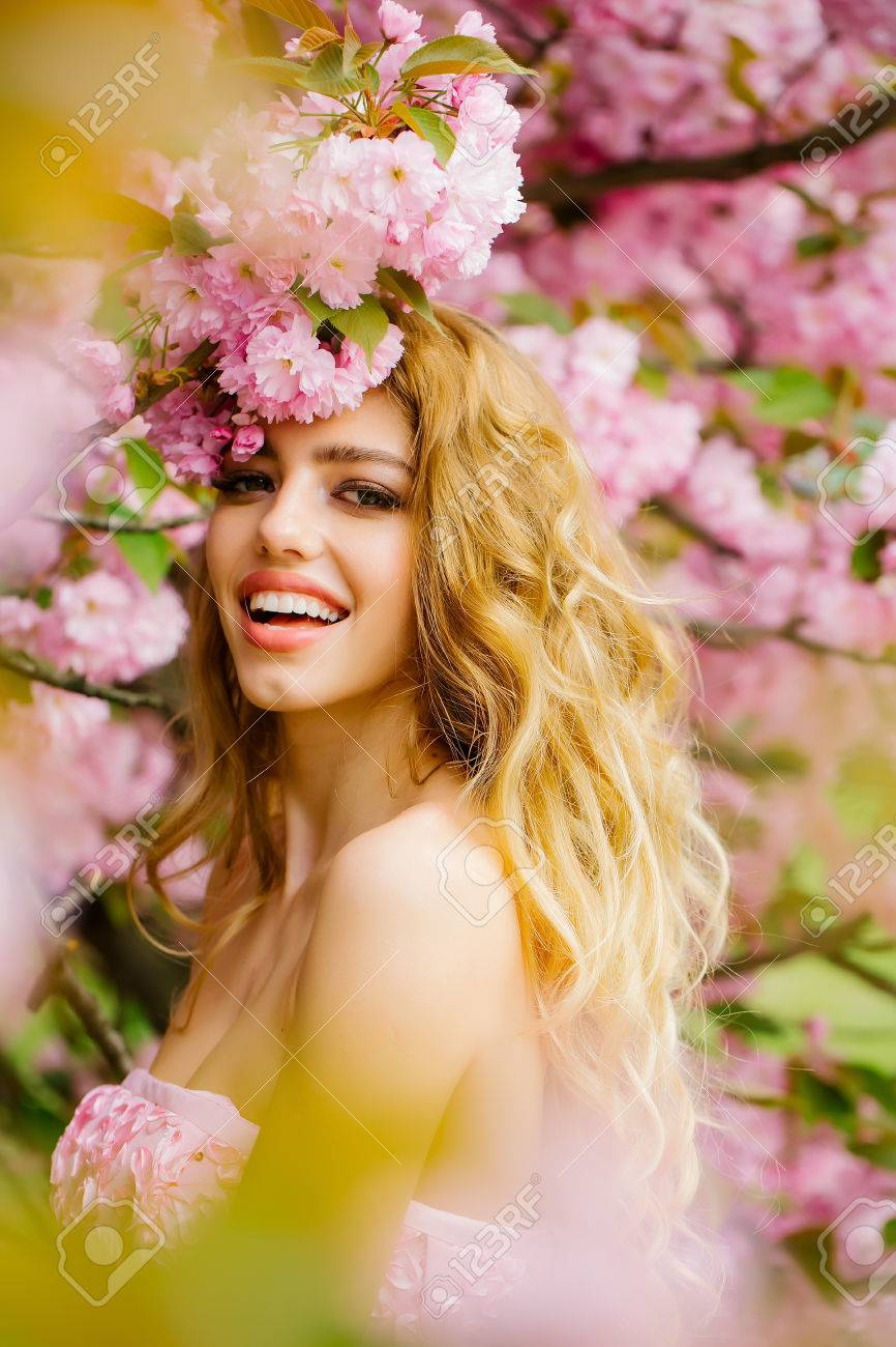 Beautiful young woman in pink glamour dress with long curly hair and smiling face in spring flowers bloom - 56087688