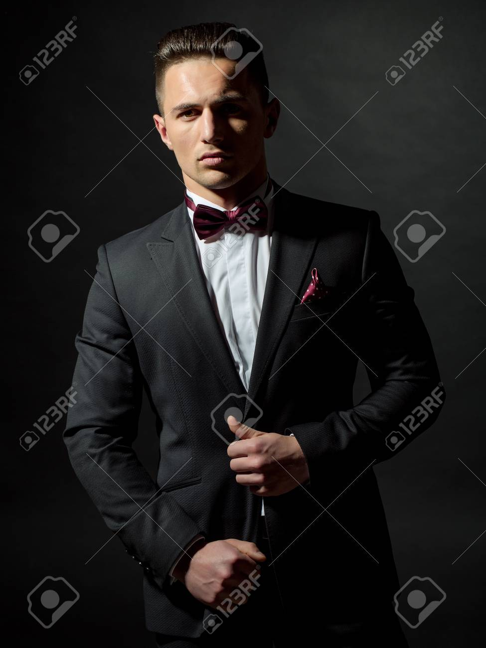 pas mal de06c 2e116 Jeune homme gentil à la mode costume noir chemise blanche et cravate au  studio