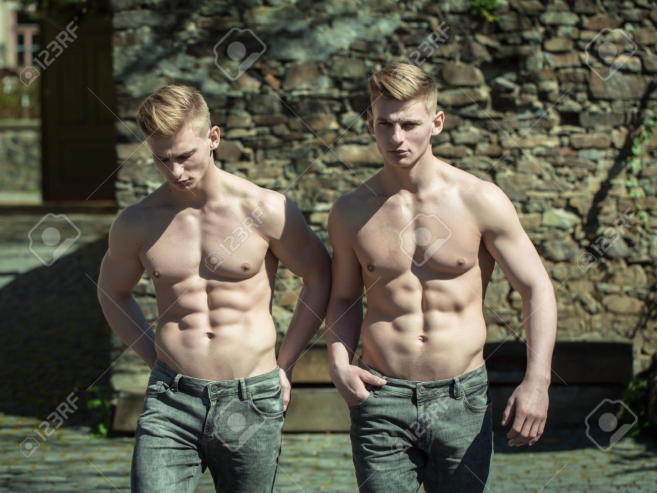 Los hombres jvenes con el torso desnudo hermanos gemelos modelos foto de archivo los hombres jvenes con el torso desnudo hermanos gemelos modelos musculares pie sin camisa en los pantalones vaqueros en el fondo del altavistaventures Choice Image