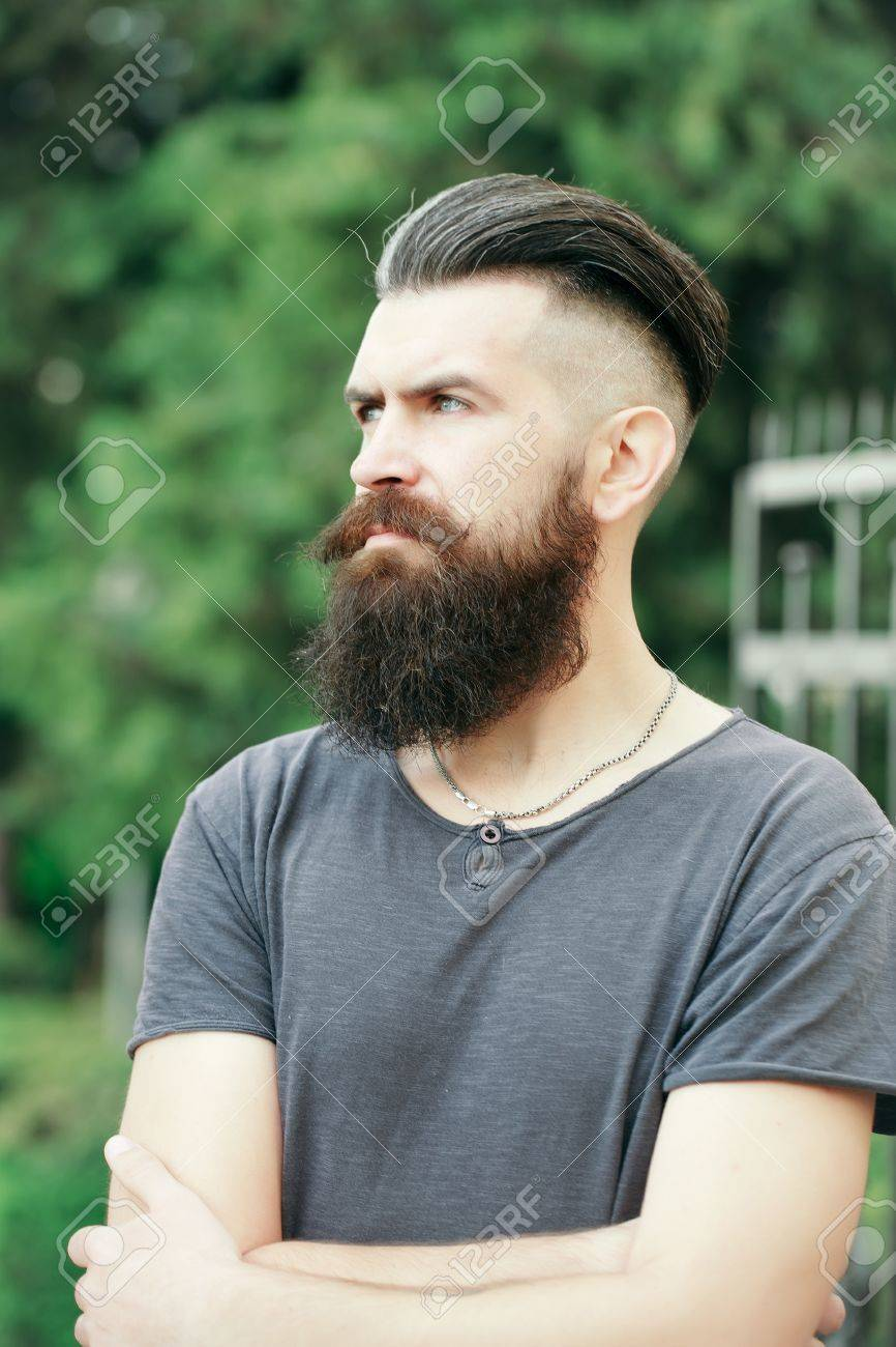 Handsome young stylish hipster man with long beard in grey shirt