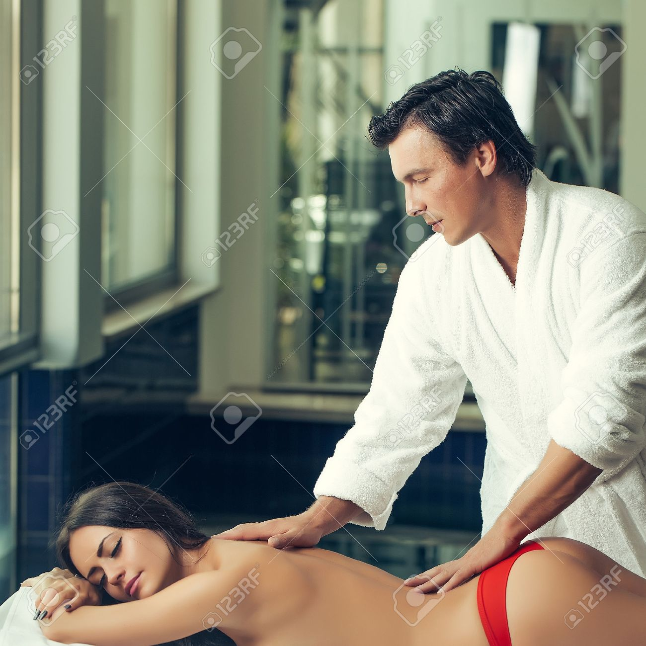 Male massage therapist in white uniform massing with hands attractive..