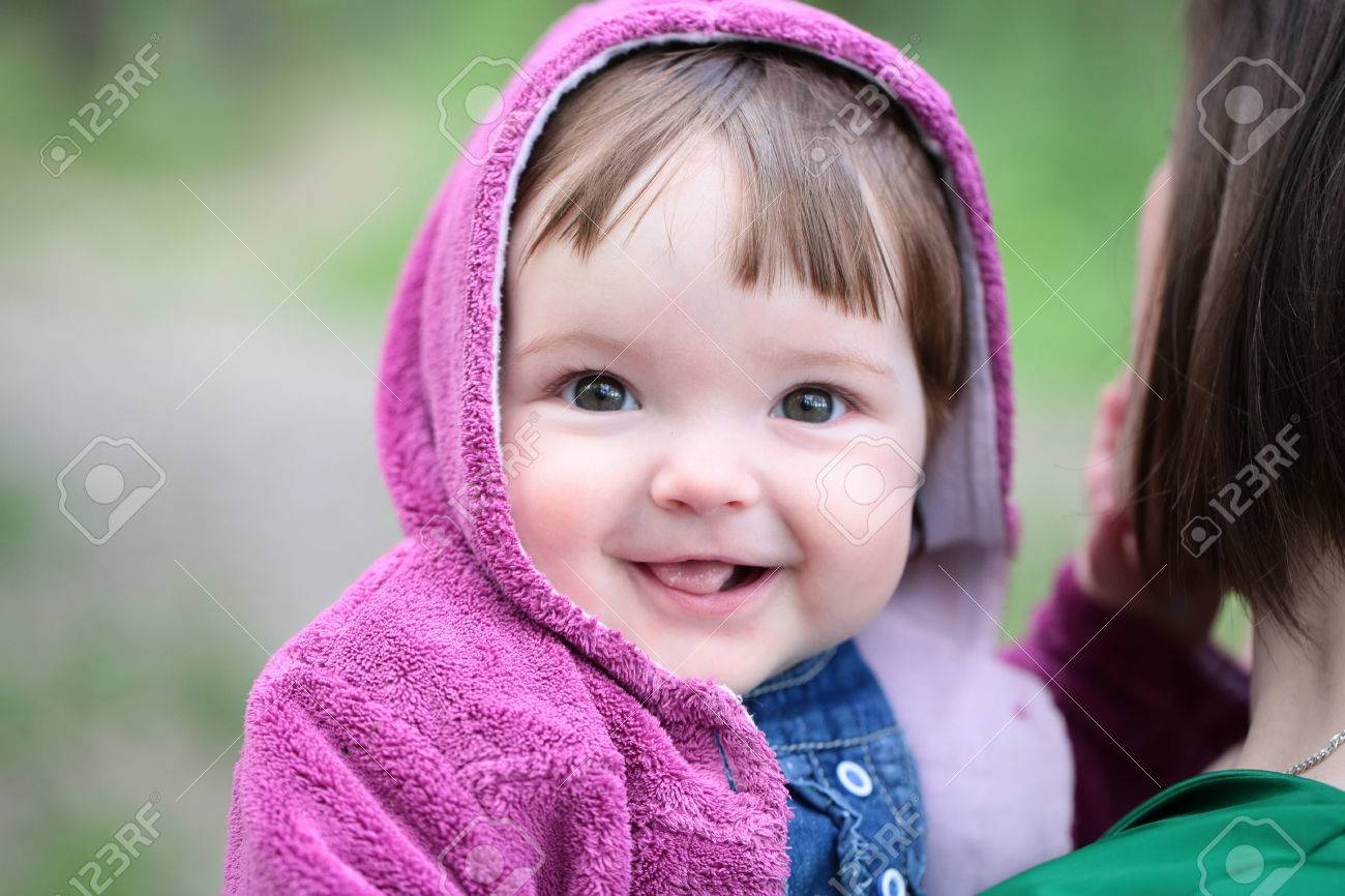 small cute baby girl with pretty smiling face and funny eyes.. stock