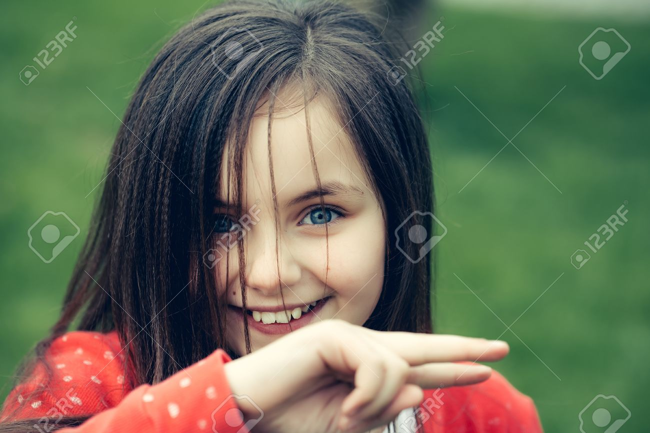 smiling face of little cute happy girl child with blue eyes and