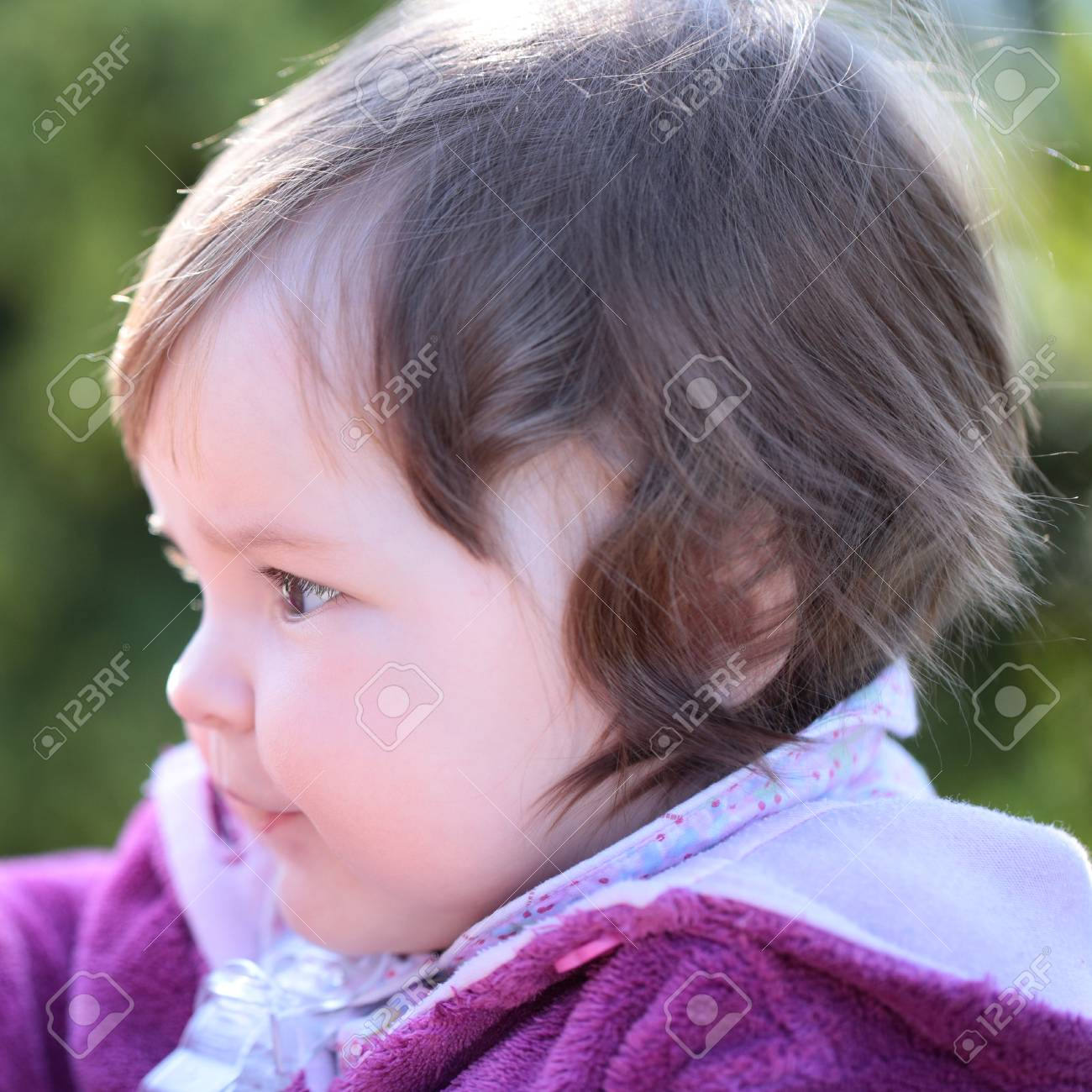 small cute baby girl with pretty face and funny eyes outdoor.. stock