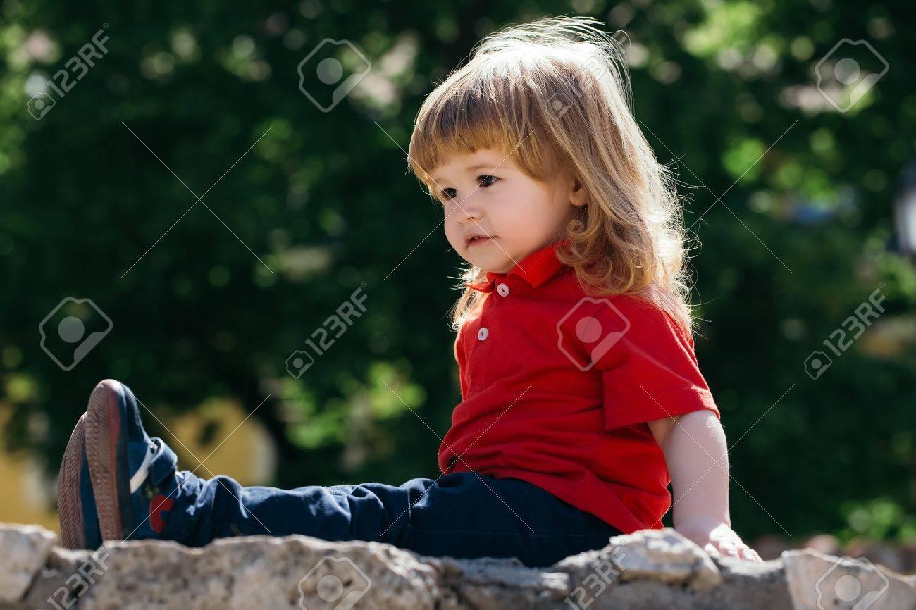 Kleine Süßen Jungen Mit Langen Haaren Auf Dem Steinzaun Lizenzfreie
