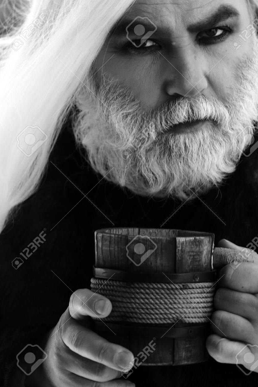 Druid old man with wrinkles long silver beard hair with wooden