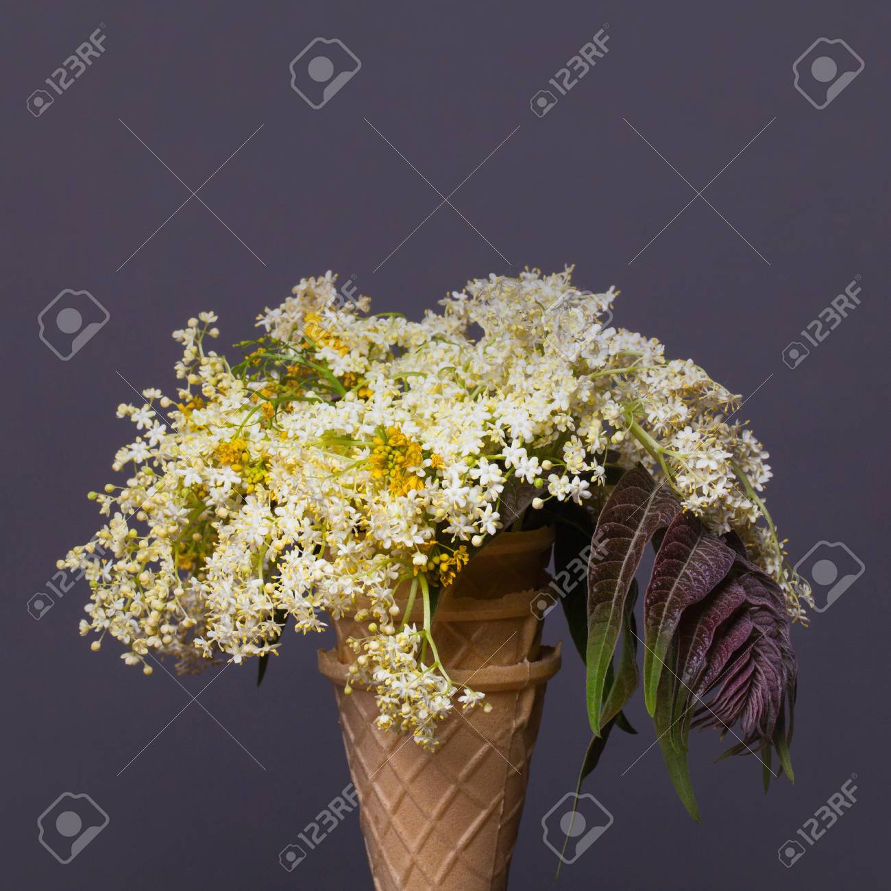 White And Yellow Flower Bouquet In Waffle Ice Cream Cone On Grey