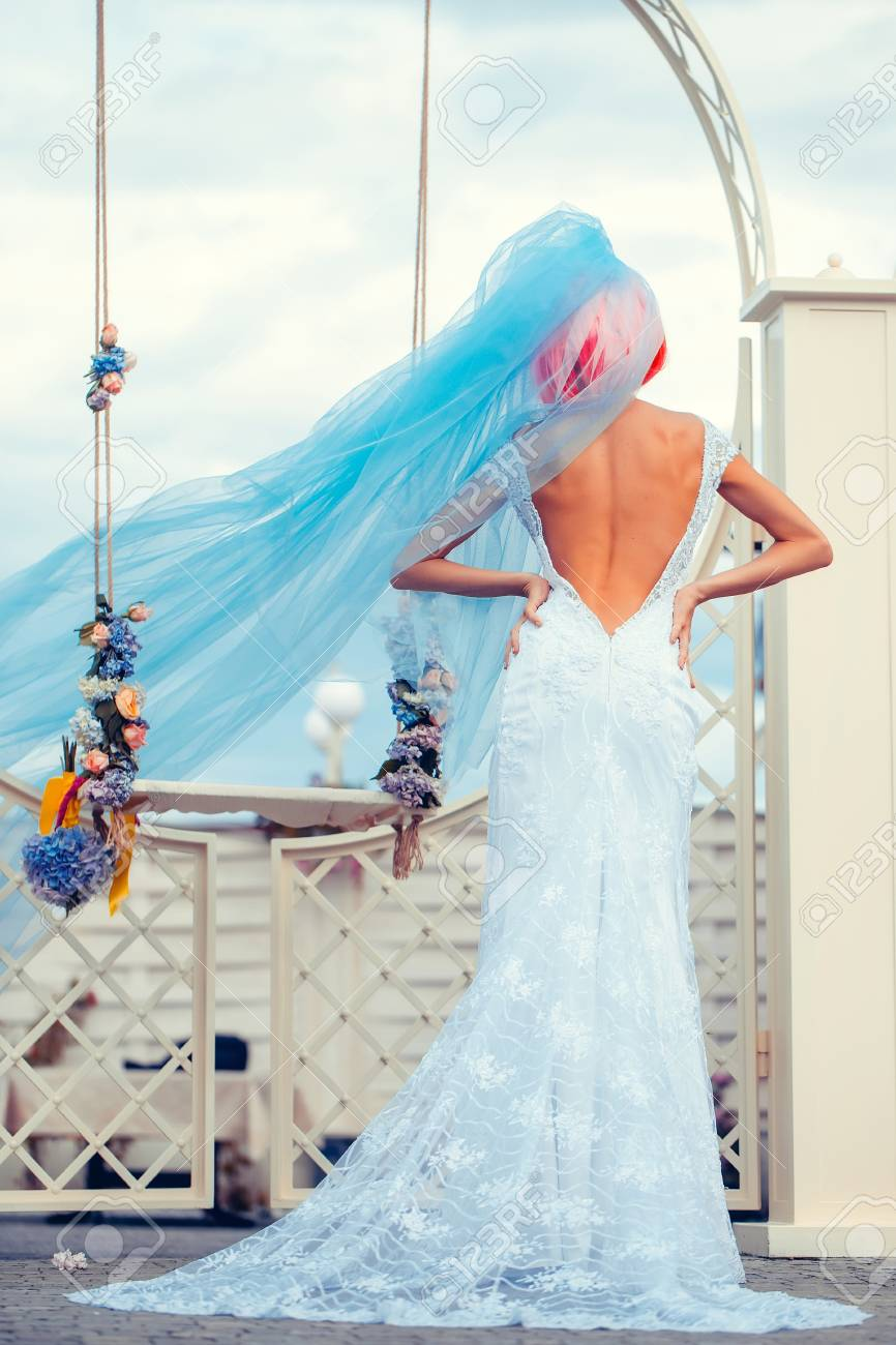 Young Woman With Orange Or Pink Hair In White Wedding Dress And