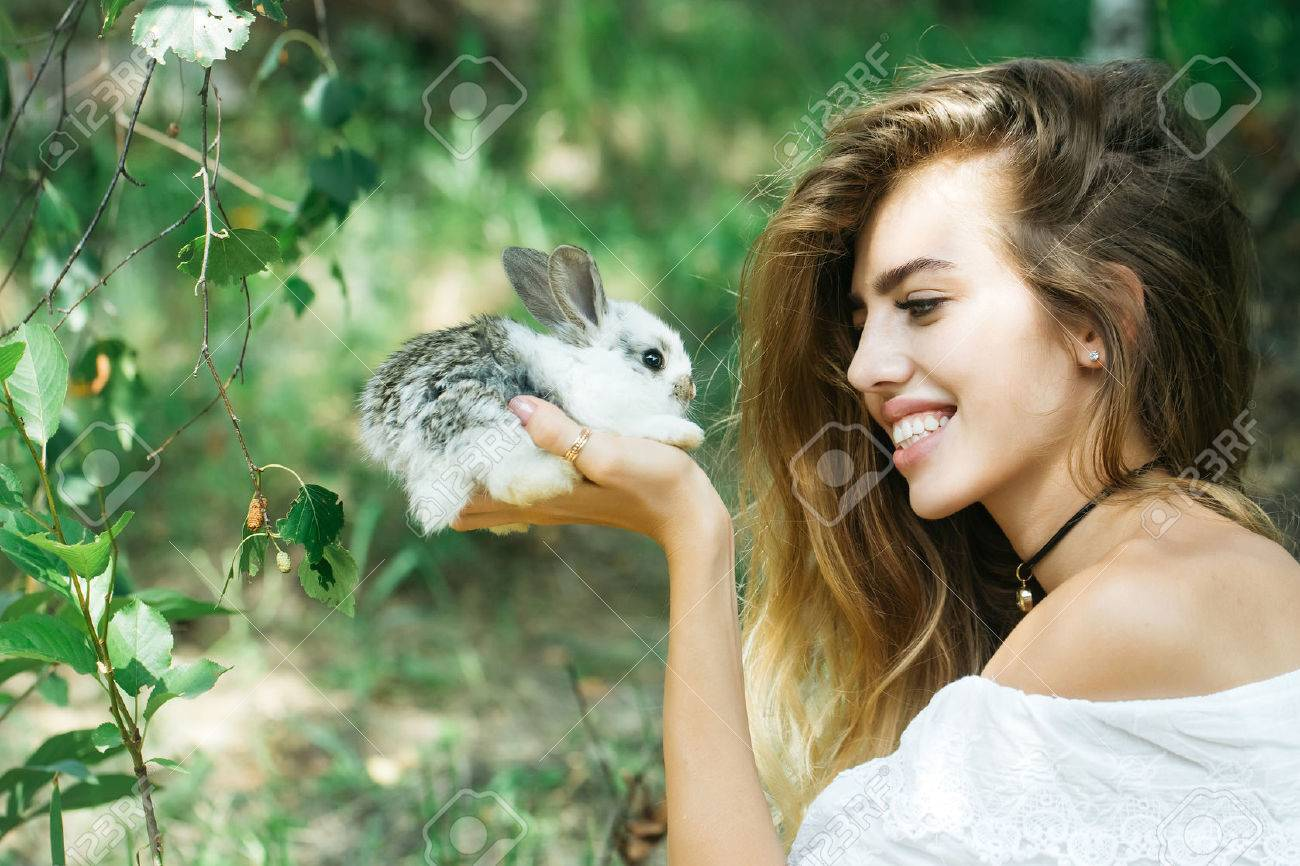 Pretty young woman long-haired holds cute little rabbit on summer day on natural background - 59938610