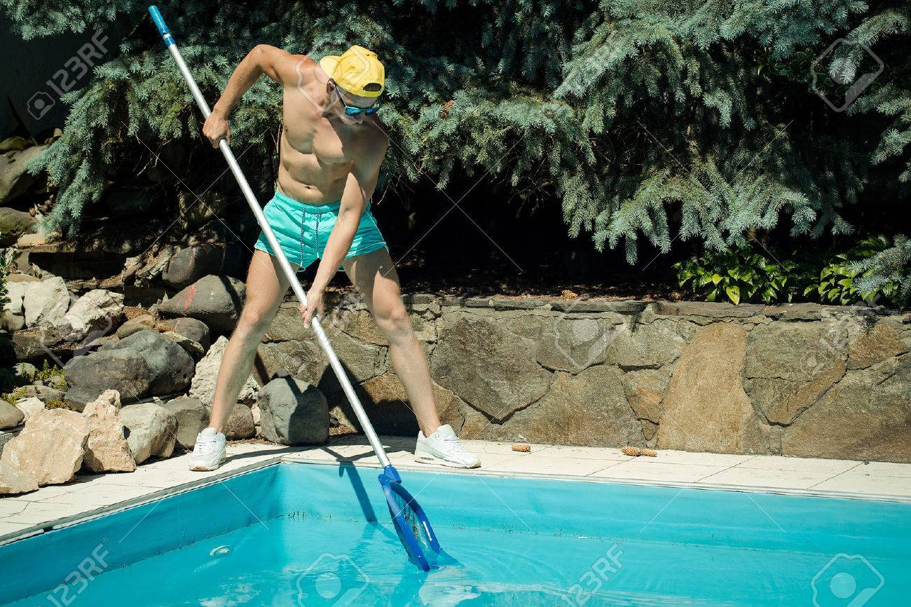 young handsome macho man cleaner with athletic muscular fit body working at swimming pool deck cleaning blue water sunny day outdoor at summer - 60441660