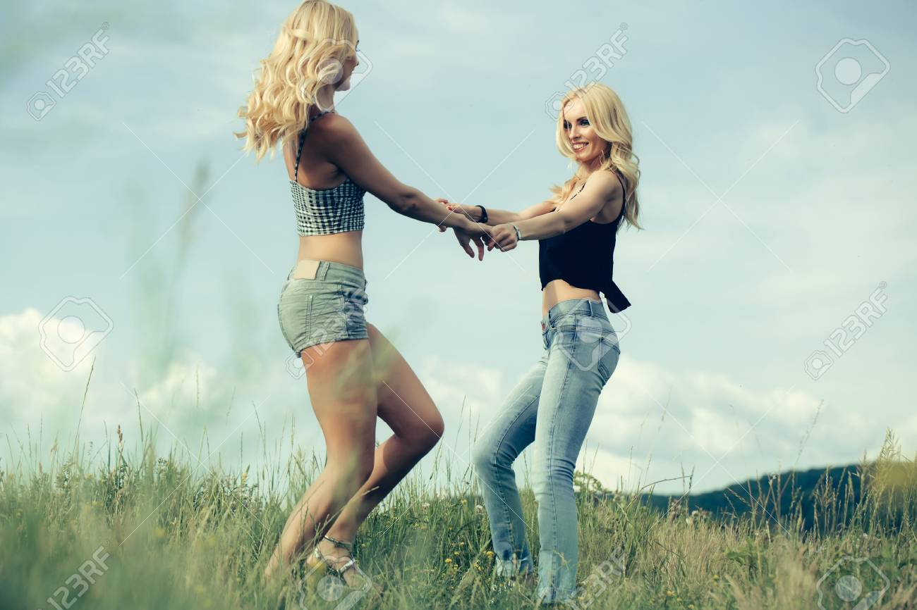 Stock Photo - young pretty women with long lush curly blonde hair and sexy  bodies standing in green field with grass and blue cloudy sky outdoor on  natural ...