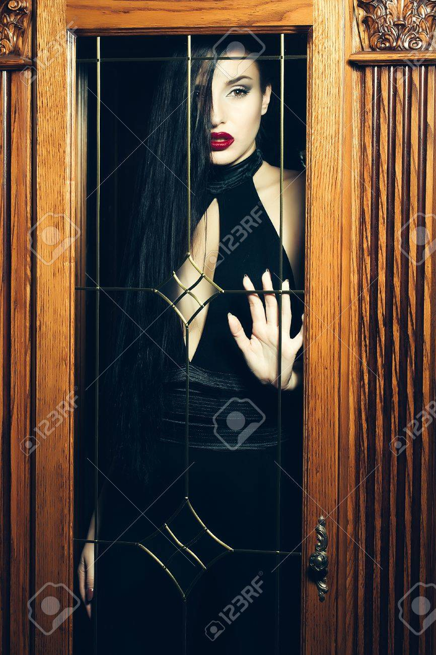 Black dress with red lipstick - Attractive Girl In A Black Dress With Red Lipstick Trapped Behind The Glass Door Stock Photo