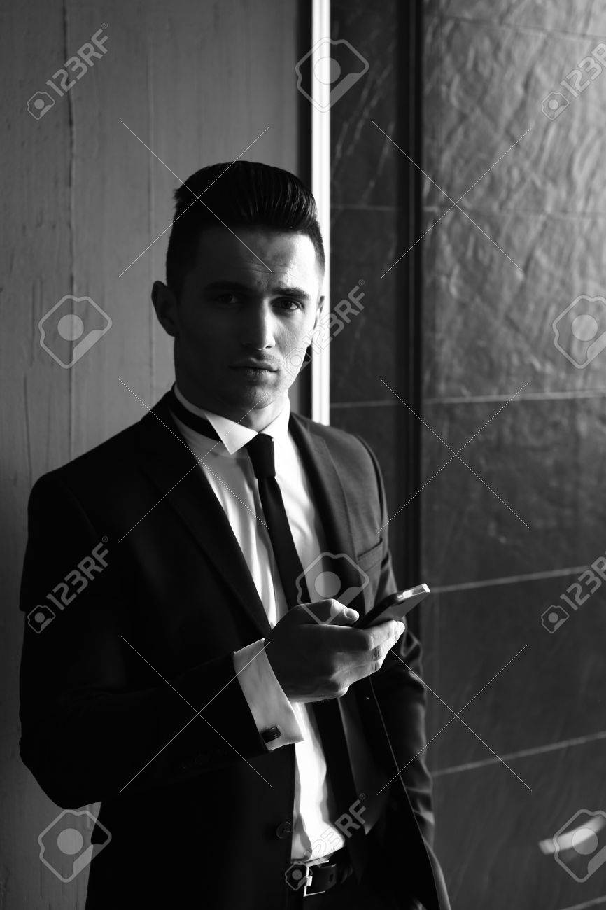 367a3829572 Man young handsome sensual elegant model in suit with skinny necktie with  smartphone looks in camera