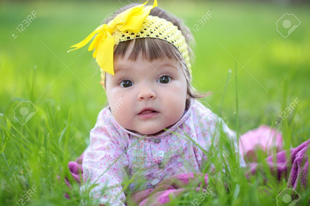 small cute baby girl with pretty face and funny eyes with yellow