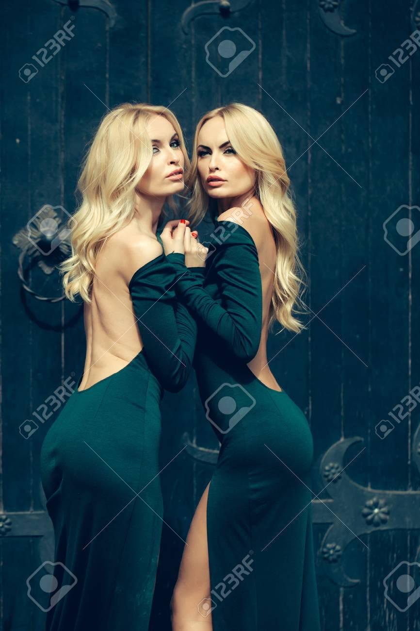 Mujeres Muy Jóvenes Con Cuerpos Largos Rizadas Rubias Exuberantes Pelo Y Atractivas En Vestidos Verdes De Pie Cerca De La Puerta Grande De Hierro