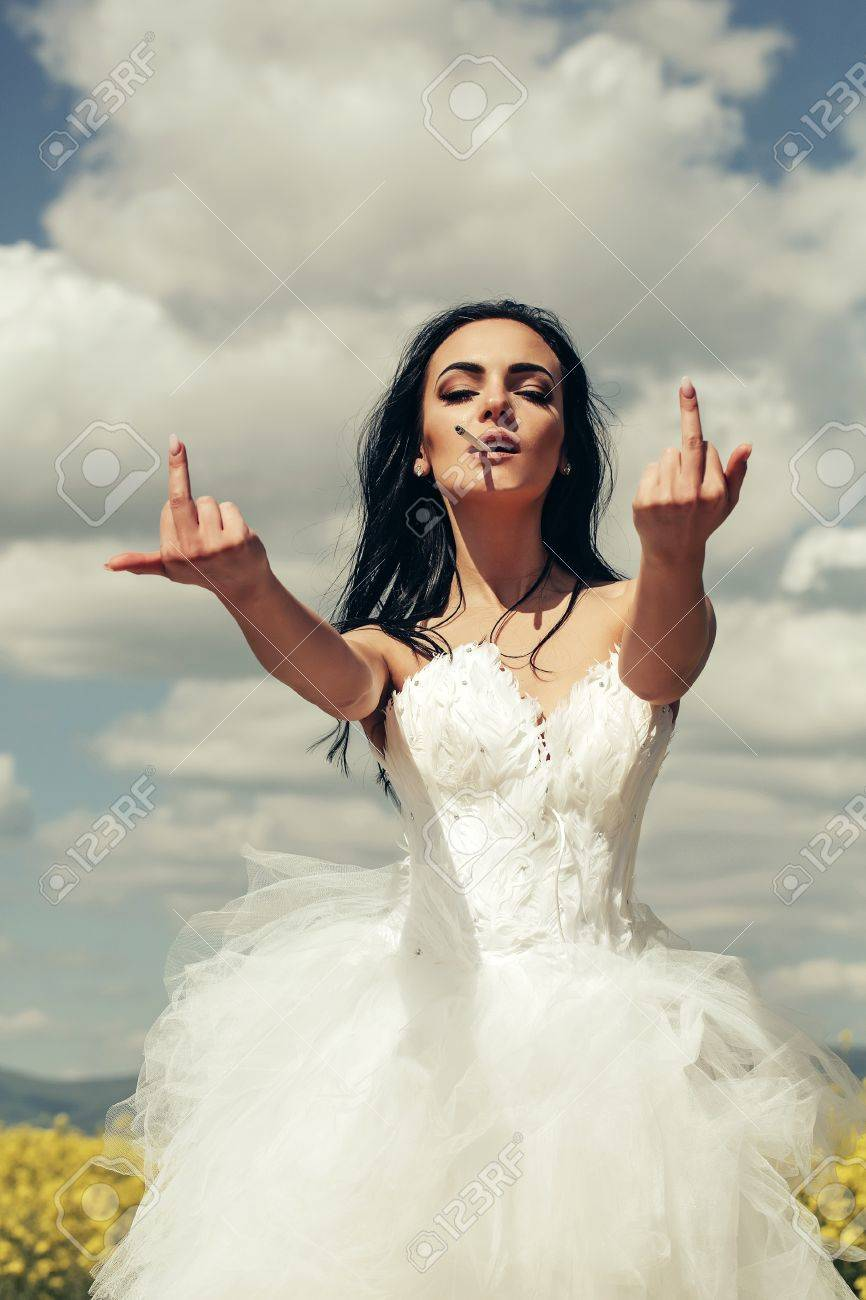 Stock Photo Young Wedding Sexy Girl Woman With Brute Hair And Pretty Face In White Bride Dress Showing Middle Fingers Smoking Cigarette On Cloudy Blue: Smoking Brides Wedding Dress At Websimilar.org
