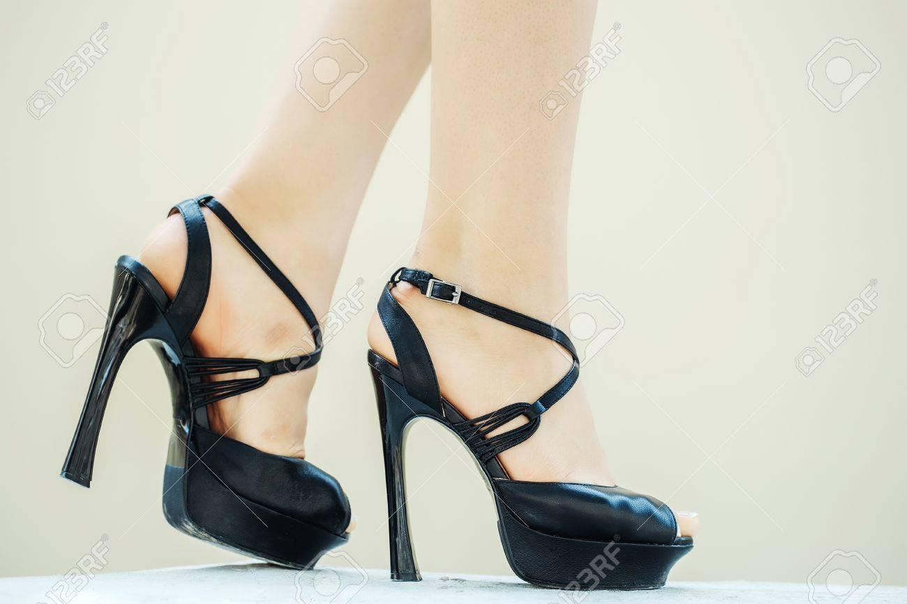 7f9b33afaf1a65 Banque d'images - Chaussures noires femmes fantaisie talons hauts pompes  sandales à lanières sur les jambes de la femme beaux pieds sur sol blanc
