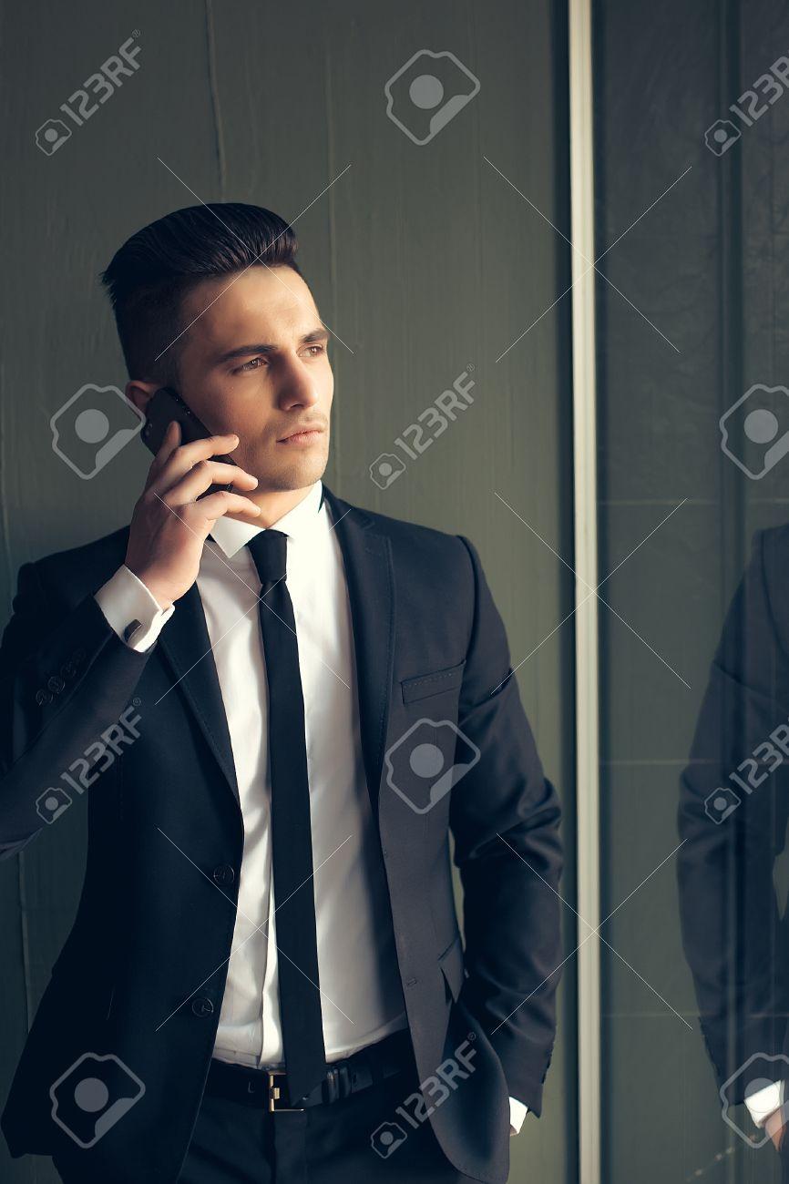 Jeune Détourne Sensuel Manteau Costume Avec Sur Modèle Maigre Des Téléphone La Cravate Élégant En Dans Discussions Homme Mobile Ouvert Main Beau gfyY6v7b