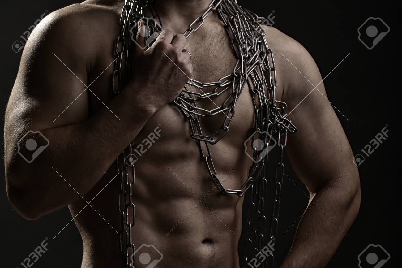 strong young man with muscular body in blue jeans holding rope