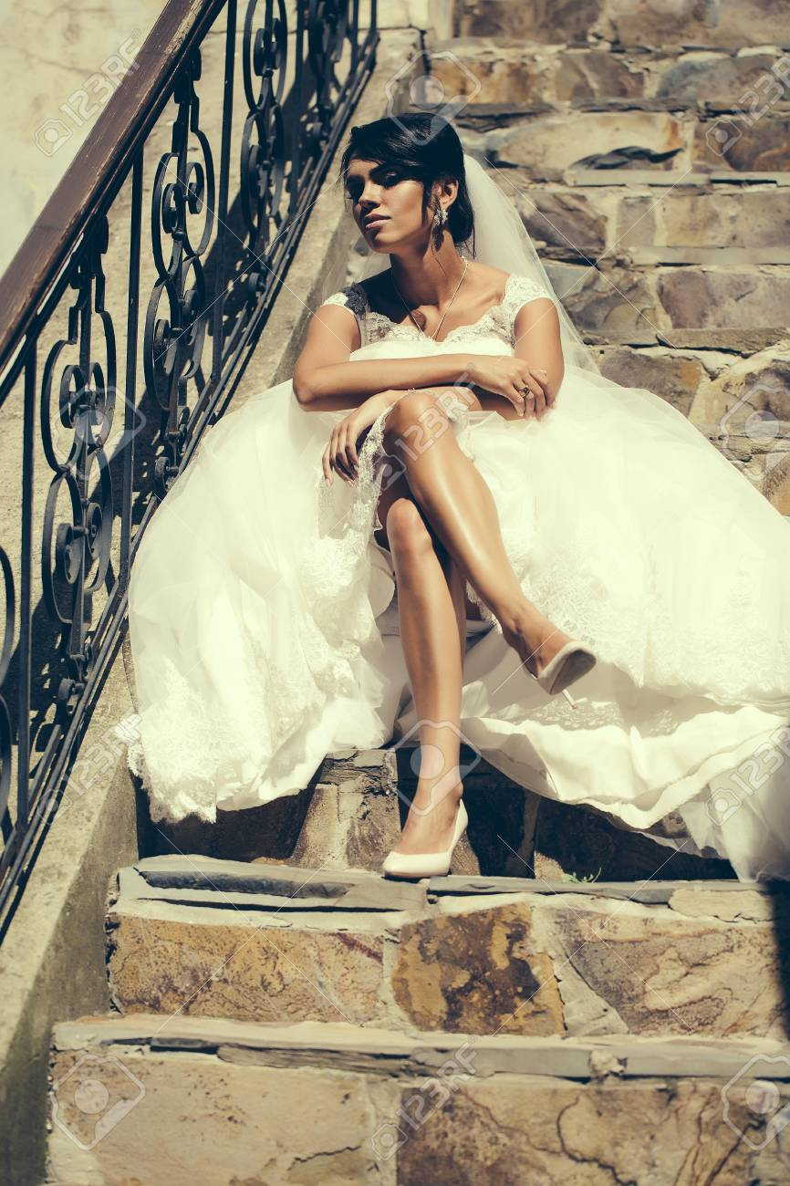 Beautiful Bride Woman With Long Sexy Legs In White Wedding Dress And Veil Sits Outdoors On: Beautiful Stone Wedding Dress At Websimilar.org