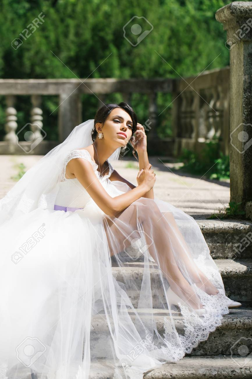 Gorgeous bride woman in elegant transparent lace wedding dress..