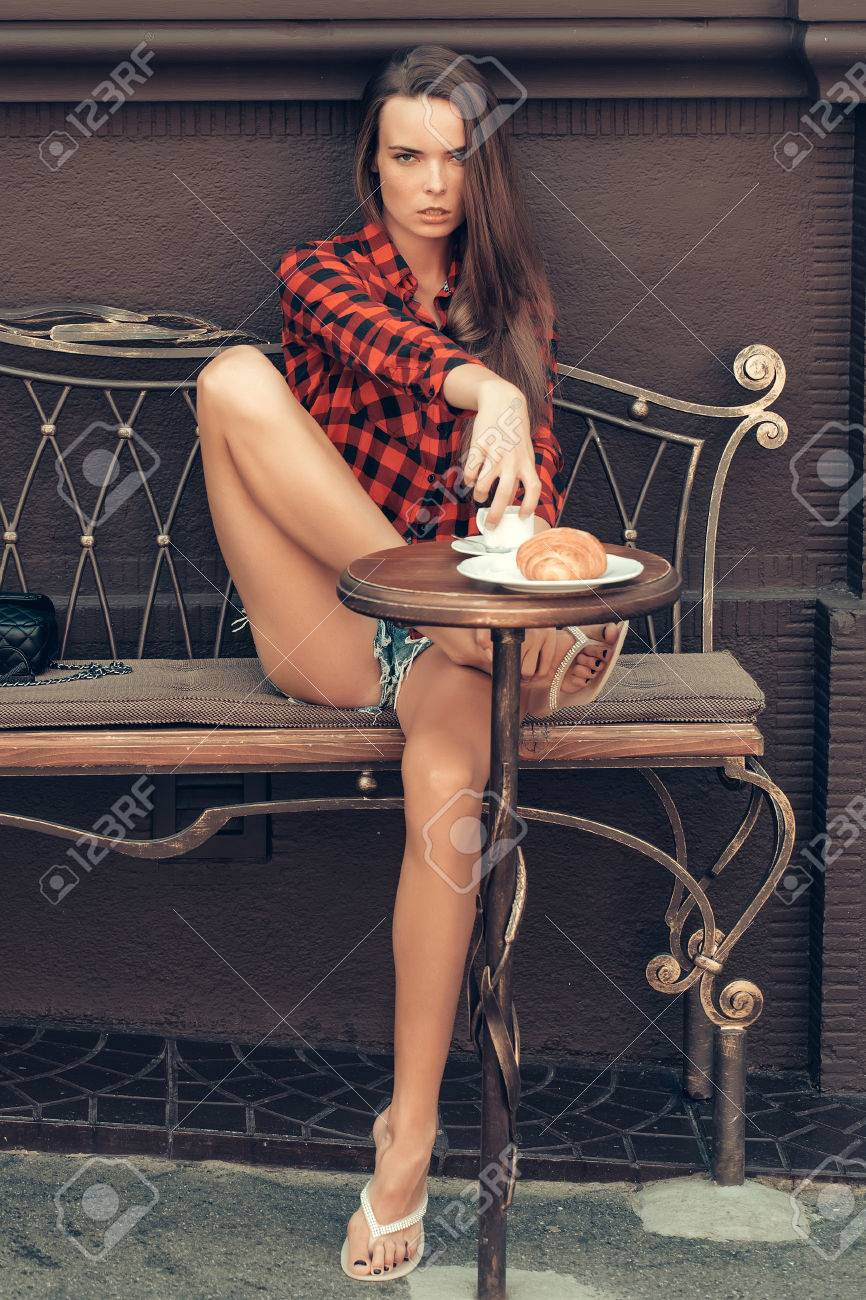 Sexy girl pretty slim model with long legs sits in red checkered shirt and  shorts on