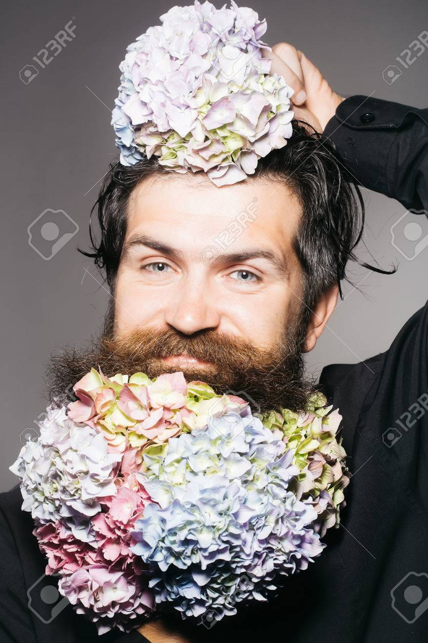 Handsome sexy bearded young man hipster with floral beard and handsome sexy bearded young man hipster with floral beard and mustache on smiling face in studio izmirmasajfo