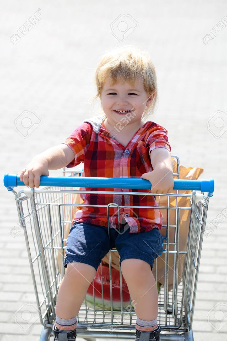 96584d37c Cute baby boy blond child in plaid shirt sits in shopping trolley and eats  cookie from